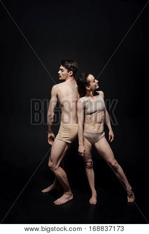 Art performance of two dancers. Concentrated thoughtful talented performers dancing in the studio and expressing emotions while taking part in the art performance against black background