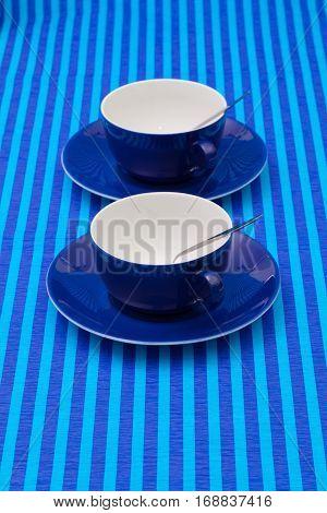 Symmetry arrangement empty cups of tea on blue striped tablecloth. Blue concept.
