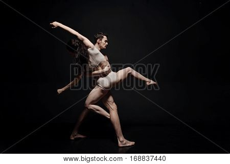 Forming a single whole. Creative inspired masterful performers performing in the studio and dancing while taking part in the art performance against black background