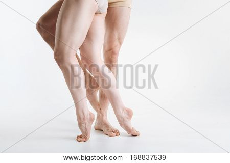 Elegant ballet dancers legs . Gracile elegant athletic ballet dancers legs located in the white colored studio and demonstrating dancing pa