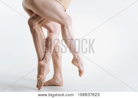 Professionalism in details. Tensed sinewy muscular ballet dancers legs located in the white studio and being tensed while standing on the white floor