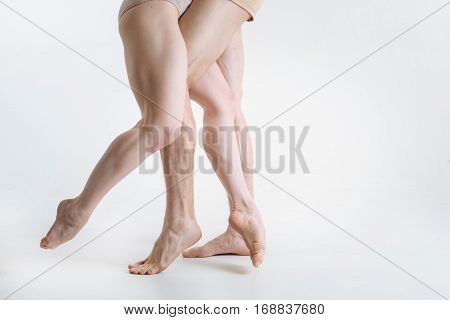Elegance in details. Tensed athletic muscular ballet dancers legs located in the white studio and being tensed while performing on the white floor