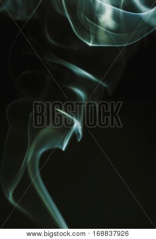 Blue smoke waves closeup on dark background.