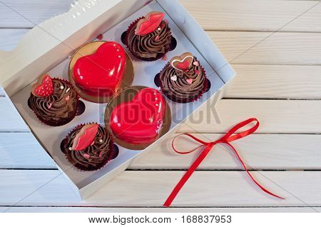 confectionery. Brown cupcakes red glazed mousse hearts and small honey cakes in box lay on white wooden table near red bow knot. Focus on red cakes