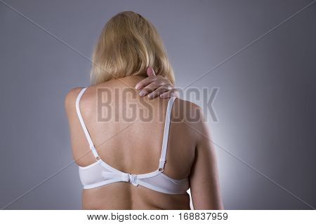 Neck pain massage of female body ache in woman's body on gray background