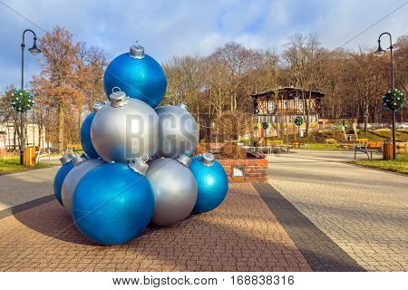 TRZEBNICA, POLAND - DECEMBER 28, 2016: Christmas baubles decoration in the park of Trzebnica, Poland. The town lies in the historic Lower Silesia region, 20 kilometres of the regional capital Wroclaw.