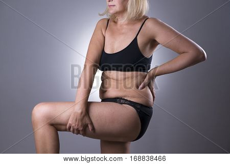 Woman in black lingerie overweight female aging body on gray studio background