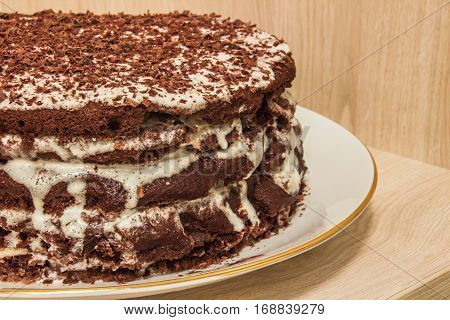 Сhocolate cake is soaked in sour cream and decorated with chocolate shavings