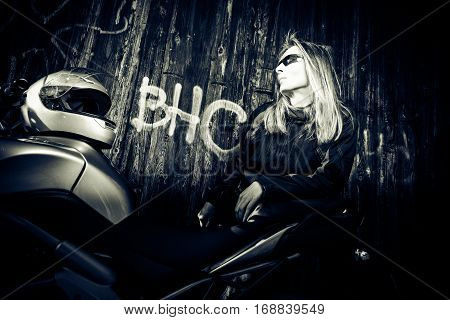 an adult woman is posing with her motorcycle in front of a graffiti wall. high-contrast lighting.