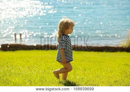 Cute Baby Boy In Striped Tshirt Walks On Green Grass