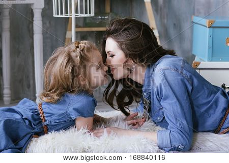 Happy Family Mother And Little Daughter Rub Against Each Other Noses Dressed In Jeans Dress