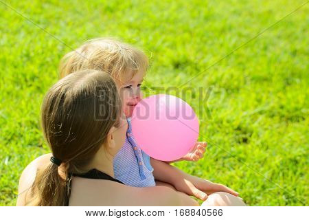 Mother and son cute baby boy with blond hair play with pink toy balloon on green grass on sunny summer day on natural background at mothers day