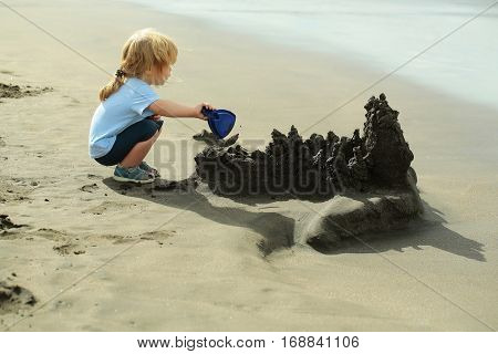 Cute baby boy with blond hair ponytail in blue tshirt and shorts builds sandcastle with shovel on sea beach on sunny summer day on seascape background