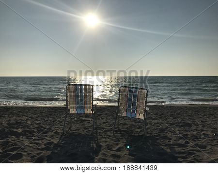 Two beach chairs looking out into the ocean.