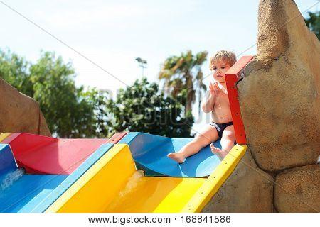Scared Cute Baby Boy Sits On Top Of Waterslide