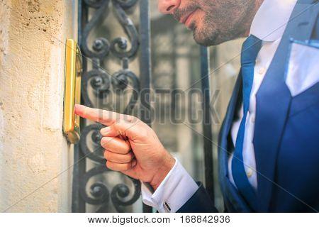 Man in suit ringing the door bell