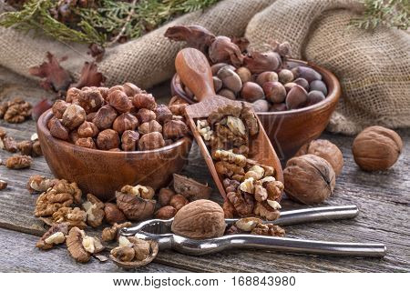 Hazelnuts and walnuts and a spoon on an old wooden table