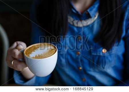 Young Beautiful Woman's Hand With Cup Of Coffee With Foam In The Form Of Leaf Blue Denim Shirt Backg