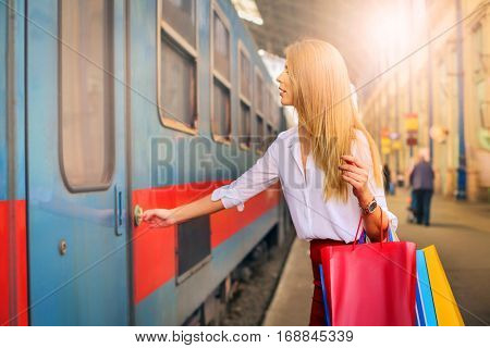 Girl with shoppingbags trying to get on the train