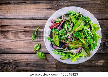 Fresh Salad With Mixed Greens On Wooden Background