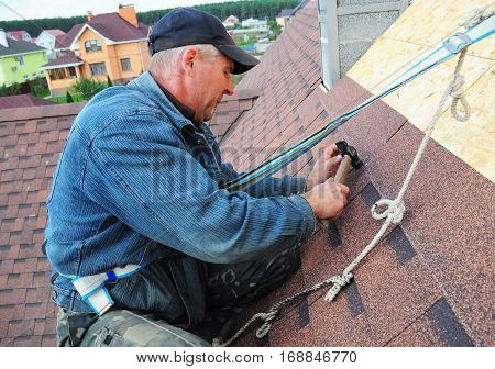 KYIV UKRAINE - February  14 2017:  Roofing Contractor. Roofing Construction and Building New House Exterior. Roofer Install Repair Asphalt Shingles or Bitumen Tiles on the Rooftop Outdoor.