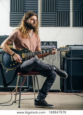 Photo of a young man with long hair and beard playing electric guitar in a recording studio.