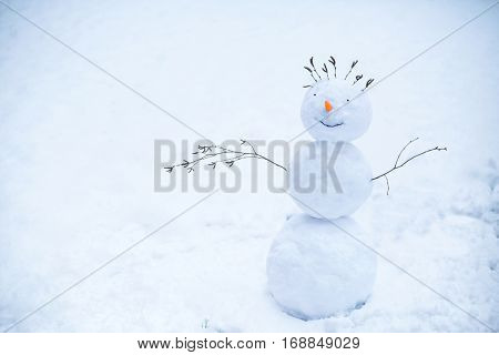 Handmade smiling snowman standing in the snow