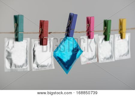 Condoms hanging on the rope on gray background.