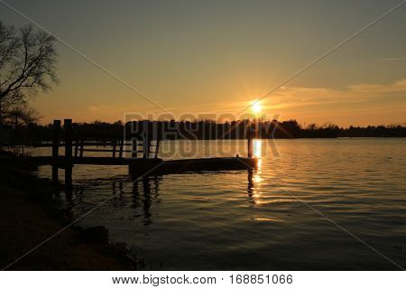 Empty dock on calm river during sunset hour.