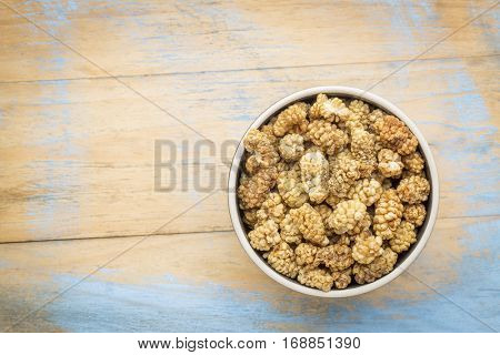 sun-dried white mulberry berries in a small ceramic bowl against grunge wood with a copy space