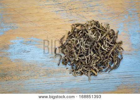Yunnan Mao Feng  loose leaf  green tea, a heap over grunge wood with a copy space, top view