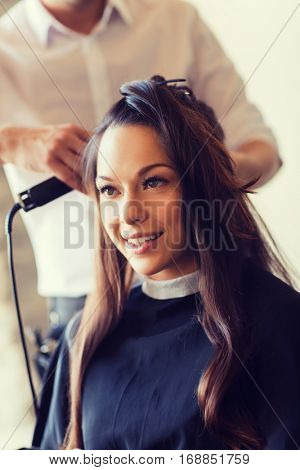 beauty, hairstyle and people concept - happy young woman with hairdresser curling hair and making hairdo at hair salon
