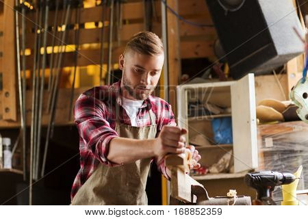 profession, people, carpentry, woodwork and people concept - carpenter working with jointer planing wood plank at workshop