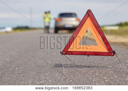road sign, emergency and traffic concept - warning triangle over broken car