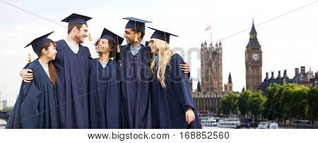 education, graduation and people concept - group of happy international students in mortar boards and bachelor gowns over london city background