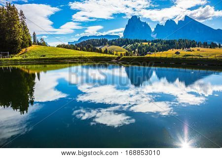 Wonderful small lake reflects the sun and jagged rocks . Well-known international ski resort in the fall. Concept of active and ecological tourism