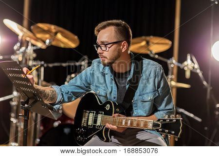 people, art, composition and entertainment concept - man with guitar writing lyrics or notes to music book at studio
