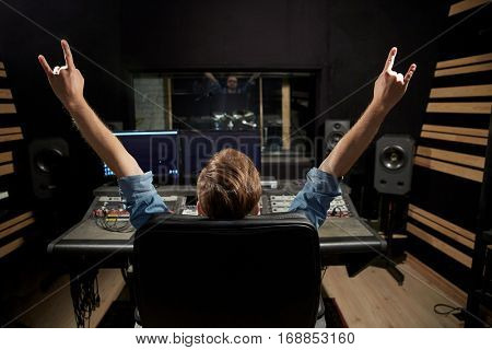 music, technology, people and equipment concept - happy man at mixing console in sound recording studio showing rock gesture