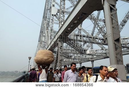 KOLKATA, INDIA - FEBRUARY 10: Morning rush hour, people crossing the Howrah bridge where bear more than 100,000 vehicles and 150,000 pedestrians everyday, Kolkata, India on February 10, 2016.