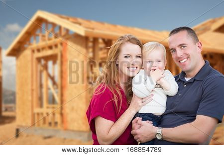 Happy Young Military Family Outside Their New Home Framing at the Construction Site.