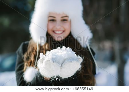 Beautiful woman in the winter park with a handful of snow