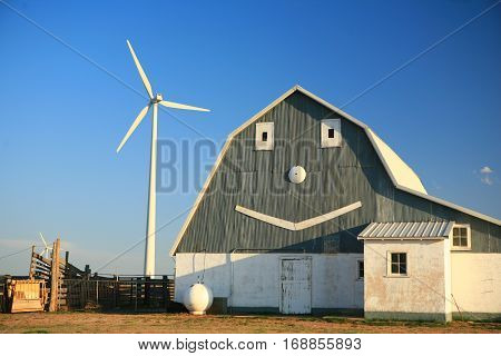 smiling face on a barn with wind generator background