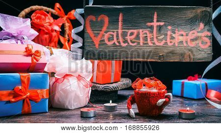 Assortment of giftboxes and valentine treats. Blue-lighted wood sign of gift shop. Valentine day concept
