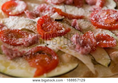 Closeup of focaccia romana with tomatoes aubergine sausage and cheese