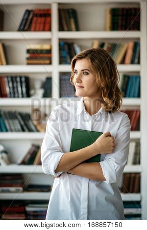 Beautiful young girl standing with book in hand in the library. Many shelves with book on a blurred background