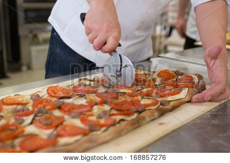 Pizza maker cutting focaccia romana with tomatoes aubergine and sausage