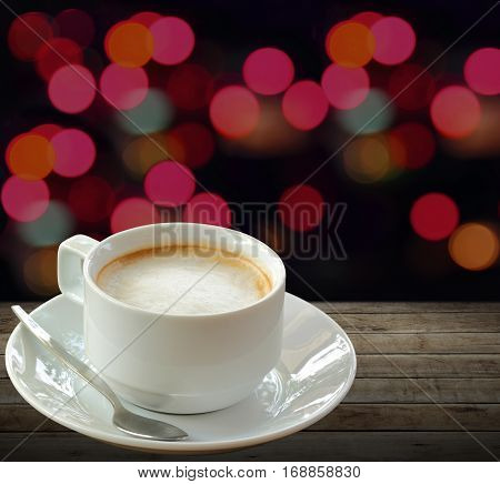 Hot coffee in white cup over wooden background with blurry night light background.