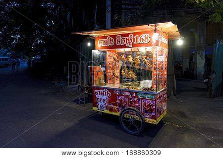 Phnom Penh, Cambodia - December 30, 2016: View of a peddler of roasted duck inside his cart, waiting for customers along a street of capital city of Cambodia