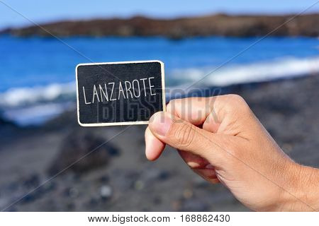 closeup of the hand of a young man holding a black signboard with the text Lanzarote written in it, in a black sand beach in Lanzarote, Canary Islands, Spain