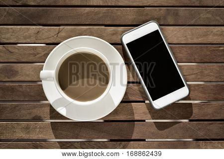 high-angle shot of a white ceramic cup with white coffee and a smartphone with the black blank screen, on a rustic wooden table